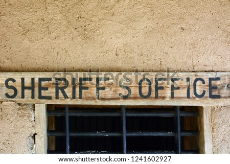 Old West Style Wooden Sign for Sheriffs Office Mounted in Adobe Wall