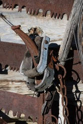 old western wooden horse stirrups hanging up with rusty saws and other rustic metal farm equipment as barn or cabin decoration in rural area outdoors