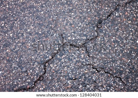 Old wet worn and cracked asphalt with cracks - stock photo