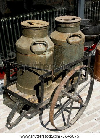 Old wheelbarrow carrying two old milk cans.