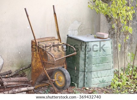 old wheelbarrow in the garden and the big green container for compost to be used as natural fertilizer for the garden ecology