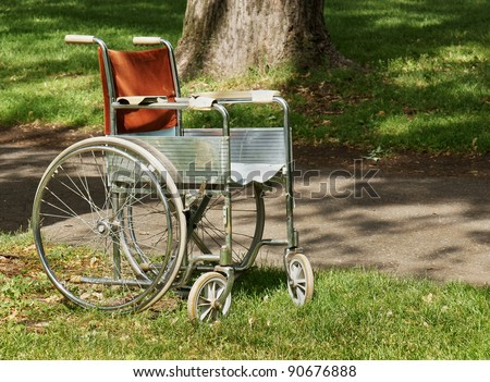 Old wheelchair abandoned in a park, perfect for aging or health background.