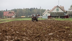 Old wheeled tractor on rural plowed field, farming work, soil cultivation on an autumn day on brick village houses and forest background, beautiful countryside agriculture landscape