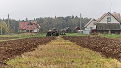 Old wheeled tractor with plow on rural brown plowed field, farming work, soil cultivation on an autumn day on forest and village houses background, beautiful countryside agriculture landscape