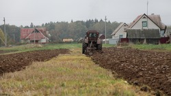 Old wheeled tractor with plow on rural brown plowed field furrow, farming work, soil cultivation on an autumn day on forest and village houses background, beautiful countryside agriculture landscape