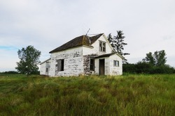 Old white abandoned house in the middle of a field in Saskatchewan, Canada.