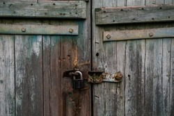 Old white and blue wooden door with a rusty metal lock texture