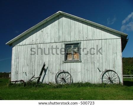 old white barn under a deep blue sky