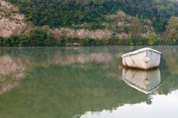 Old white boat on lake