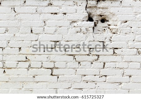 old white brick wall with holes....