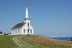 old white church in nova scotia, canada, overlooking the sea on summer's day