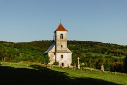 Old white church in the countryside. Abandoned house bell tower. Panorama of green landscape with a church. Red roof church. Blue sky spring meadow.