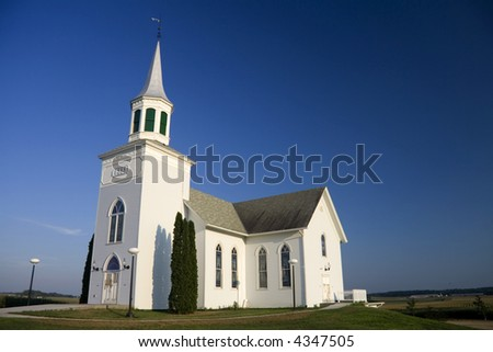 Old white church set against a dark blue sky