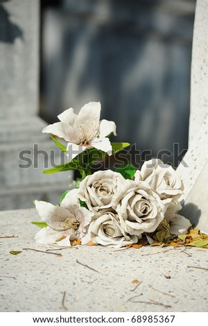 old white fake flower on grave