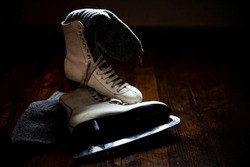 Old, white ice skates on the wooden floor. Winter sports