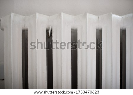 Old white iron radiator close up. Pipes and a white heating radiator heat the room. Retro heat radiator. Cast iron household radiator close up.