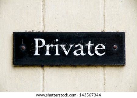 Old white on black private sign screwed to a door