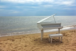 Old white piano on a sandy beach.  Beidaihe, China