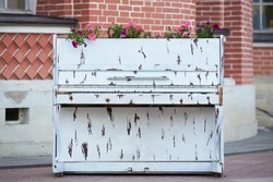 Old white piano with flowers for garden decorations
