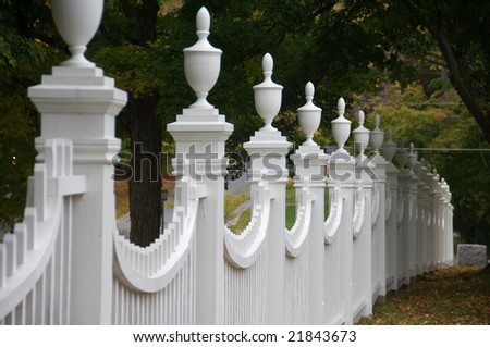 Old white picket fence in an autumn landscape.