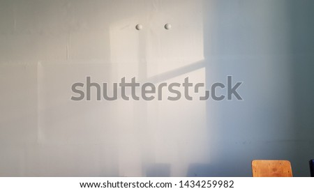 Old white plastering wall surface with blurry geometric shadows and top of wooden chair in corner. Cross shaped shadows with two round dots. Crossed lines shadow background. Light and shadow backdrop.