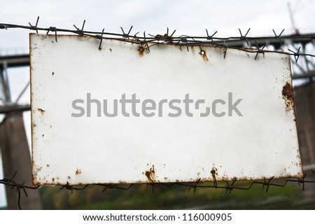 Old white plate on a barbed wire fence
