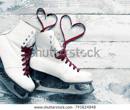 Old white skates for figure skating with a hearts of laces on a vintage wooden surface. Concept of love. #795824848