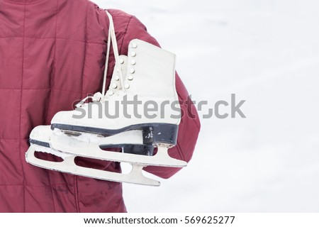 Old white skates over shoulder in winter day. Weekends activities outdoor in cold weather. #569625277