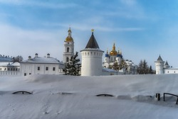 Old white-stone Tobolsk Kremlin (Siberia, Russia) on a very cold clear winter day. Many churches with golden domes and towers, thick defensive walls with observation towers and a large snowdrift
