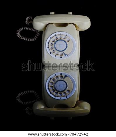 Old white telephone isolated on black background.
