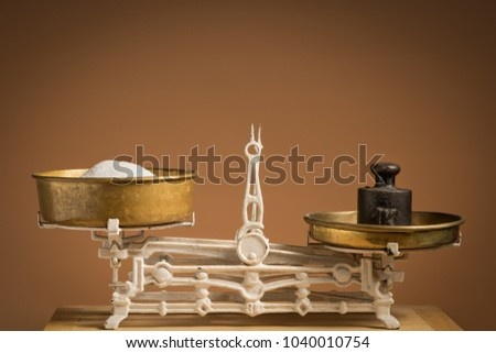 Old white vintage kitchen scale, brass with weights and sugar on a kitchen table