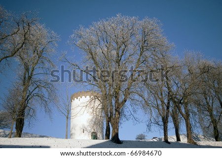 Old white water tower in winter snow
