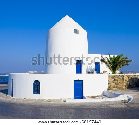 old white windmill on the hillside near the road on the island of Mykonos
