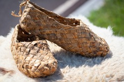 Old wicker bast shoes made of wood.