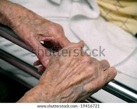 Old wife's hands by the bed