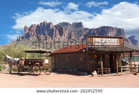 Old Wild West Cowboy town with horse drawn carriage and mountains in background