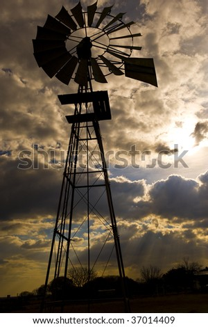 Old windmill against a dramatic cloudscape in the late afternoon with the sun coming through the clouds.  Intentional under-exposure on the foreground to create a silhouette. - stock photo