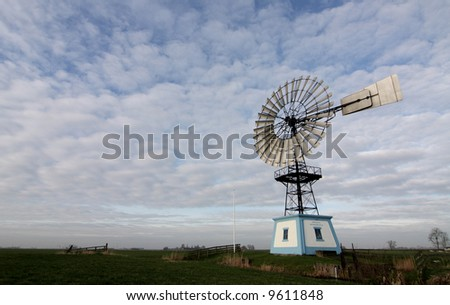 old windmill in field with cloudy sky