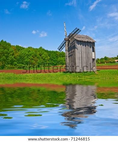 old windmill on a lake coast