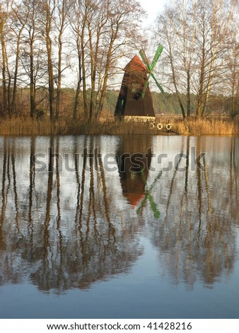 old windmill was built as a tourist attraction built on the island of a small lake in the village Zielona in Poland
