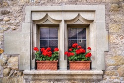 Old window in a medieval house wall with red geranium on the windowsill