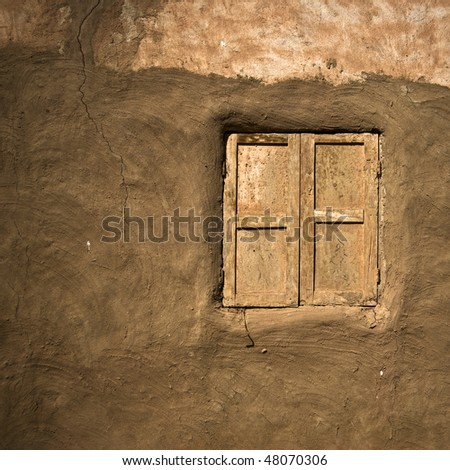 Old window on mud wall in oasis town, Egypt - stock photo