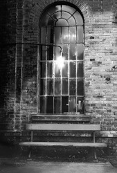 Old Window with  bench in front of brick wall in an old train station in black and white