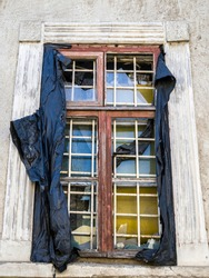 Old window with broken glass. The black protective foil is torn and is hanging in clumps. The building is in disrepair.