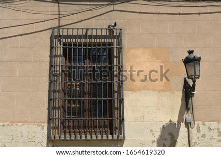 old window with wooden shutters and rusty fence and lapposst on a chipped wall in a building in Madrid. Spain