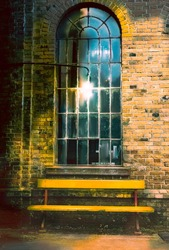 Old Window with yellow bench in front of brick wall in an old train station