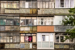Old windows and balconies. Facade of a dilapidated house of post-Soviet architecture