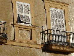 Old windows in old Mediterranean style architecture. A pretty cast iron balcony with its silhouette from bright sunshine. Two shutters are open on a slant. The wall is unusually tiles in two patterns
