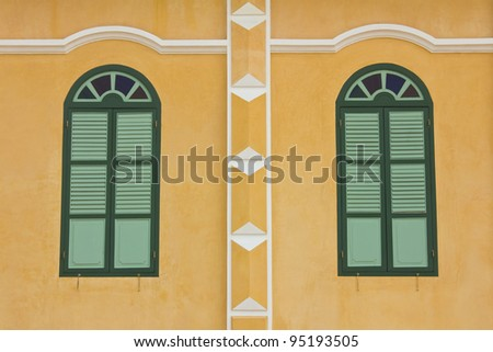 old windows on the yellow wall