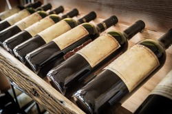 Old wine bottles on the wine shelf. Wine cellar.